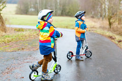 Two little kid boys, best friends riding on scooter in park Royalty Free Stock Photos
