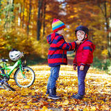 Two little kid boys with bicycles in autumn forest Royalty Free Stock Image
