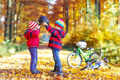 Two little kid boys with bicycles in autumn forest Stock Image