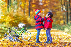 Two little kid boys with bicycles in autumn park Stock Images