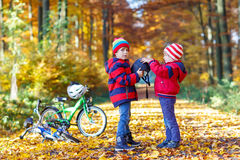 Two little kid boys with bicycles in autumn park Stock Photography