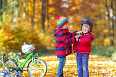 Two little kid boys with bicycles in autumn park Stock Image