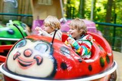 Two little kid boys on carousel in amusement park Stock Photos
