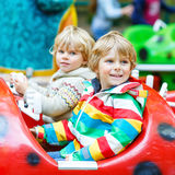 Two little kid boys on carousel in amusement park Royalty Free Stock Photo