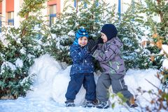 Two little kid boys in colorful clothes playing outdoors during snowfall. Active leisure with children in winter on cold days. Hap Stock Images