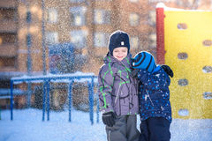 Two little kid boys in colorful clothes playing outdoors during snowfall. Active leisure with children in winter on cold days. Hap Stock Image