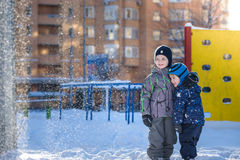 Two little kid boys in colorful clothes playing outdoors during snowfall. Active leisure with children in winter on cold days. Hap Stock Photography