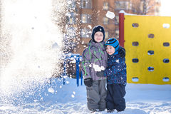 Two little kid boys in colorful clothes playing outdoors during snowfall. Active leisure with children in winter on cold days. Hap Stock Photo