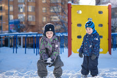 Two little kid boys in colorful clothes playing outdoors during snowfall. Active leisure with children in winter on cold days. Hap Stock Photos
