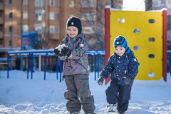 Two little kid boys in colorful clothes playing outdoors during snowfall. Active leisure with children in winter on cold days. Hap Royalty Free Stock Photo