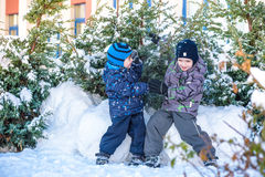 Two little kid boys in colorful clothes playing outdoors during snowfall. Active leisure with children in winter on cold days. Hap Royalty Free Stock Photos