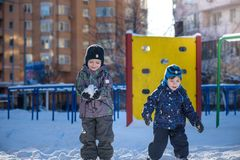 Two little kid boys in colorful clothes playing outdoors during snowfall. Active leisure with children in winter on cold days. Hap Royalty Free Stock Image