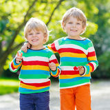 Two little kid boys in colorful clothing walking Royalty Free Stock Image