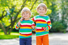 Two little kid boys in colorful clothing walking hand in hand Royalty Free Stock Photography