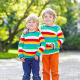 Two little kid boys in colorful clothing walking hand in hand Stock Image