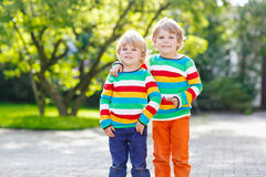 Two little kid boys in colorful clothing walking hand in hand Royalty Free Stock Photos