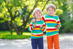Two little kid boys in colorful clothing walking hand in hand Royalty Free Stock Image