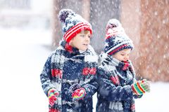 Happy children having fun with snow in winter. Two little kid boys in colorful fashion clothes playing outdoors during strong snowfall. Active leisure with stock photo