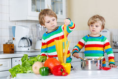Two little kid boys cooking pasta with fresh vegetables Royalty Free Stock Images