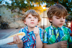 Two little kid boys eating hot dogs outdoors Royalty Free Stock Images