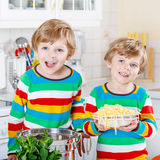 Two little kid boys eating spaghetti in domestic kitchen. Royalty Free Stock Image