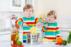 Two little kid boys eating spaghetti in domestic kitchen. Stock Photo