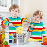 Two little kid boys eating spaghetti in domestic kitchen. Royalty Free Stock Photography