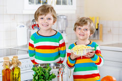 Two little kid boys eating spaghetti in domestic kitchen. Stock Images