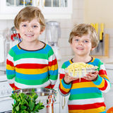 Two little kid boys eating spaghetti in domestic kitchen. Royalty Free Stock Photos