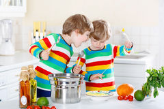 Two little kid boys eating spaghetti in domestic kitchen. Royalty Free Stock Photo