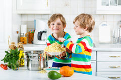 Two little kid boys eating spaghetti in domestic kitchen. Stock Photos