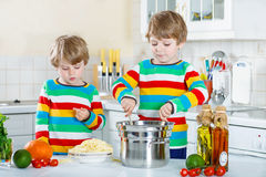 Two little kid boys eating spaghetti in domestic kitchen. Stock Image