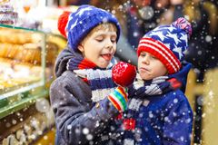 Two little kid boys eating sugar apple sweets stand on Christmas market Stock Photography