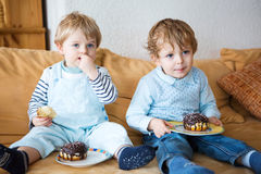 Two little kid boys eating sweet cakes together. Royalty Free Stock Photo