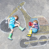 Two little kid boys with excavator chalk picture Royalty Free Stock Photos