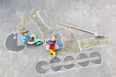 Two little kid boys with excavator chalk picture Stock Photos