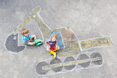 Two little kid boys with excavator chalk picture Royalty Free Stock Photography