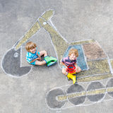 Two little kid boys with excavator chalk picture Stock Photo