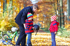 Two little kid boys and father with bicycles in autumn park Stock Photos