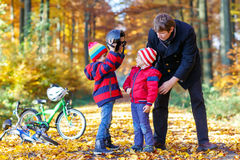 Two little kid boys and father with bicycles in autumn park Stock Photo