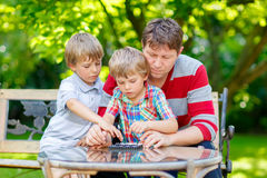 Two little kid boys and father playing together checkers game Royalty Free Stock Photo
