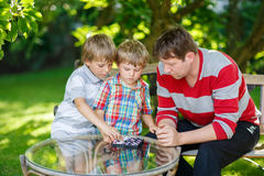 Two little kid boys and father playing together checkers game Royalty Free Stock Image