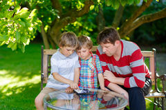 Two little kid boys and father playing together checkers game Stock Photography