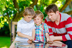 Two little kid boys and father playing together checkers game Stock Photo