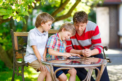 Two little kid boys and father playing together checkers game Stock Image