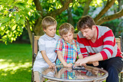 Two little kid boys and father playing together checkers game Royalty Free Stock Photos