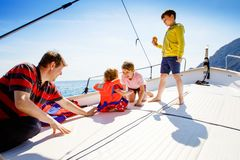 Two little kid boys, father and toddler girl enjoying sailing boat trip. Family vacations on ocean or sea on sunny day stock photos