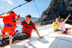 Two little kid boys, father and toddler girl enjoying sailing boat trip. Family vacations on ocean or sea on sunny day royalty free stock photos