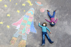 Two little kid boys flying by a space shuttle chalks picture. Two Funny little kid boys flying in universe by a space shuttle picture painting with colorful Stock Images