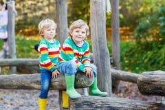 Two little kid boys having fun on autumn playground Royalty Free Stock Image